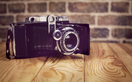Vintage camera on wooden and brick  background