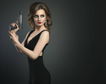 Sexy beauty young woman with gun on a dark bg portrait