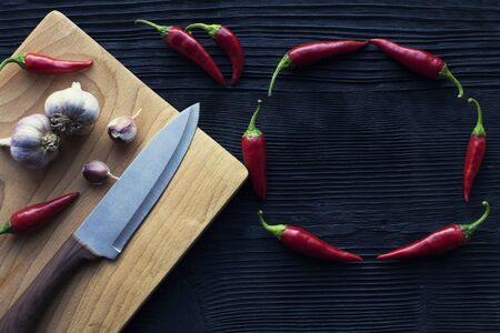 knife garlic wooden board chili on a dark background Banco de Imagens