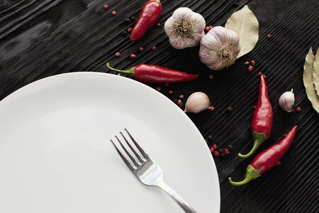 Plate fork garlic red chili on black wooden background