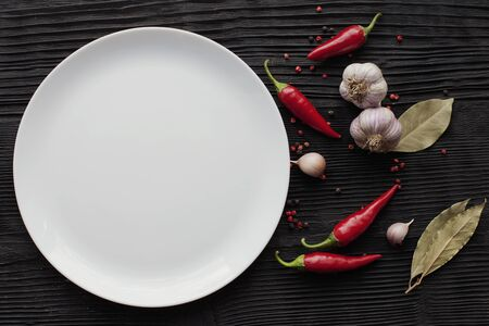 Plate garlic red chili on black wooden background Banco de Imagens