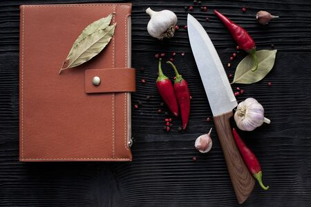chef  knife garlic  chili and notepad  on a wooden dark background