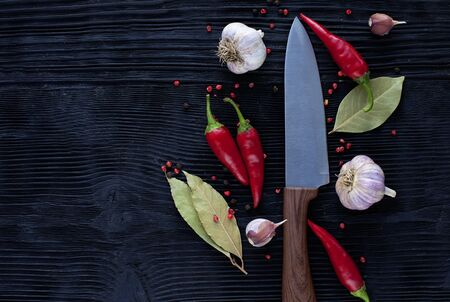 chef  knife garlic  chili on a wooden dark background
