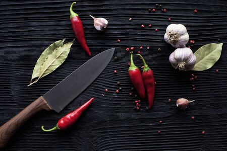 chef  knife garlic chili on black wooden background Banco de Imagens