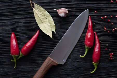 chef  knife garlic red chili on black wooden background Banco de Imagens