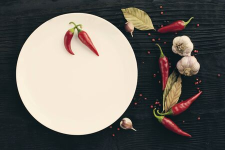 White plate garlic red chili pepper on black wooden background Banco de Imagens
