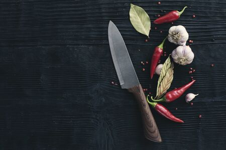 Chef  Knife garlic red chili pepper on black wooden background Banco de Imagens