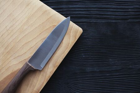 Chef knife cuting board on  black wooden background Banco de Imagens