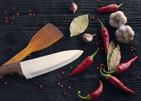 Knife chef garlic red chili pepper on black wooden background Banco de Imagens