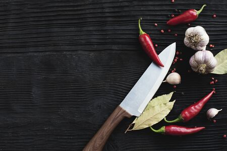 Knife garlic red chili pepper on black wooden background Banco de Imagens