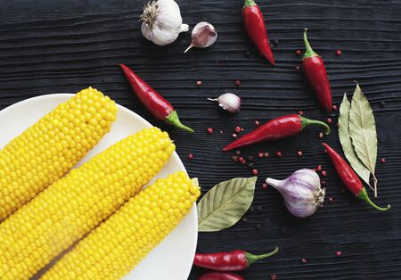 Spice red chili pepper and corn on  black wooden background Banco de Imagens
