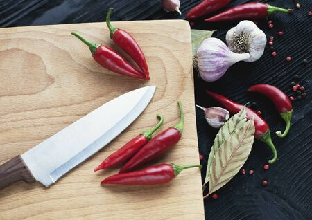Chef knife  red chili pepper and spice on  wooden background