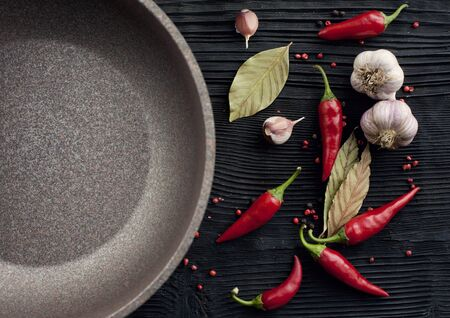 Garlic red chili pepper pan on black wooden background