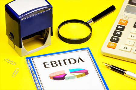 EBITDA-a text inscription on the letterhead of the folder and a graph indicator of the company's valuation. Calculator for calculations, printing and pen for visa documents.