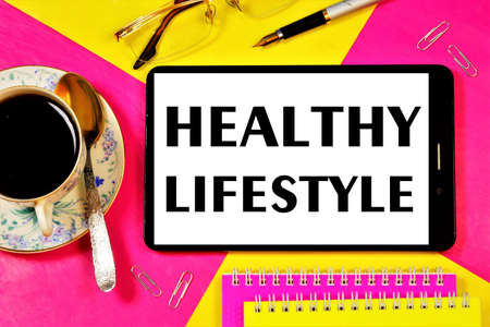 A healthy lifestyle is the inscription of text on the screen of a smartphone and a Cup of healthy drink. Promotes financial and cultural well-being.