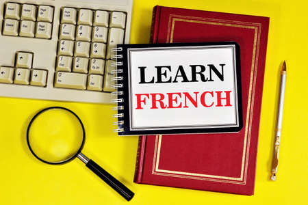 Learn French. - writing text in a notebook on a textbook. Learning spelling grammar and conversational practice. Reklamní fotografie