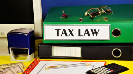 Tax law-text inscription on the folder of the office Registrar against the background of office supplies.