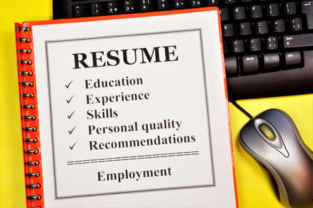 Resume. The document is in a folder on the keyboard. Professional qualities that are important for a successful career: education, knowledge and skills.