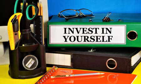 Invest in yourself. Lettering of the text in the folder on the background of stationery. Placement of capital for the purpose of obtaining financial profit or knowledge in education.