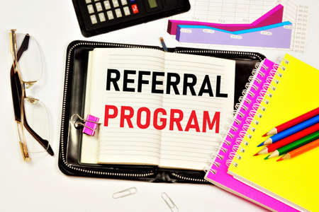 Referral program. Text label in the planning notebook. The affiliate marketing scheme is common on the Internet on sites that provide services.