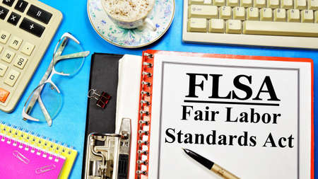 FLSA. The Fair Labor Standards Act. Text label on the folder. Guaranteed right to a minimum wage and overtime pay. Banco de Imagens