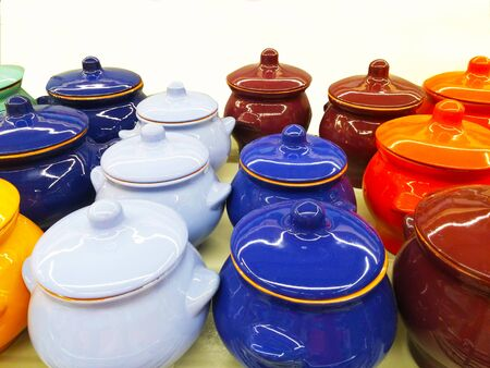 Colorful small pots for cooking. White, blue, brown, orange pots for cooking