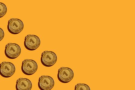 Background of gold medals with a hard shadow.