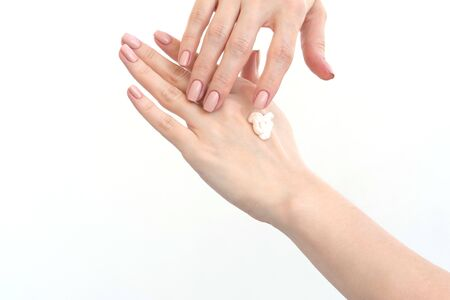 Close-up of a drop of cream on female hands. Moisturizing hands. Skin care on a white background Stock Photo