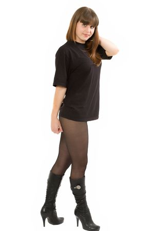 The young beautiful girl in a black T-shirt and black stockings on a white background. Isolated Stock Photo - 6101473