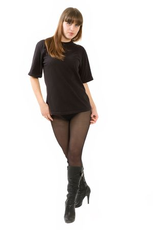 The young beautiful girl in a black T-shirt and black stockings on a white background. Isolated Stock Photo - 6101476