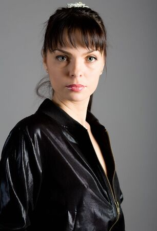 young beautiful woman in a black jacket on a grey background photo