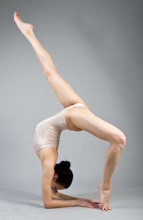 gimnasia: joven gimnasta hermoso sobre la formaci�n. El maestro de los deportes.