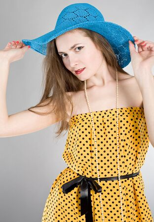 Portrait of the girl in a yellow dress and a dark blue hat photo