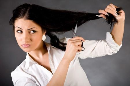 La giovane bella ragazza tagli fuori le forbici di capelli scuri