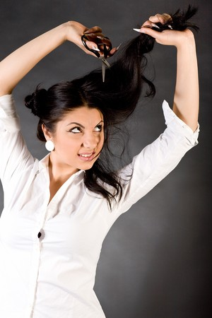 The young beautiful girl cuts off the dark hair scissors Stock Photo - 7314536