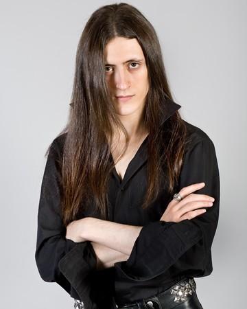 Portret van de jonge man met lang haar in zwarte kleren