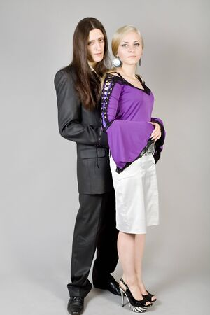 The young guy in a black suit and the girl in an elegant dress photo