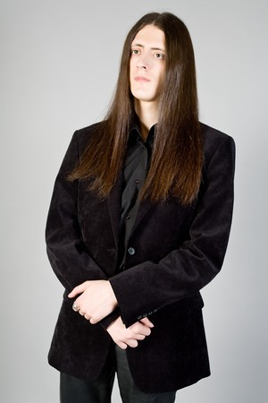 Portrait of the young man with long hair in black clothes photo