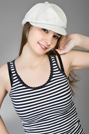 striped vest: attractive brunette in a white cap and a striped vest Stock Photo