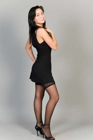 young attractive girl in a black dress on a gray background photo