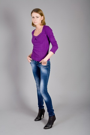 The beautiful young girl in jeans and a blouse photo