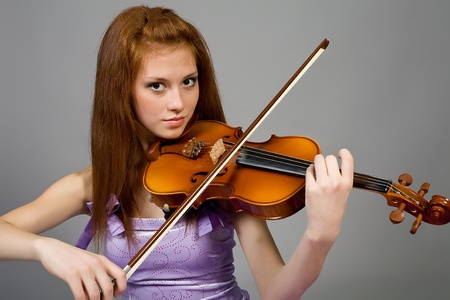 violin player: The young attractive girl with a violin