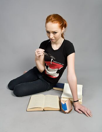 attractive red-haired girl with books Stock Photo - 12336272