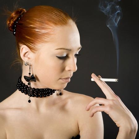 young elegant girl with a cigaret on a black background photo
