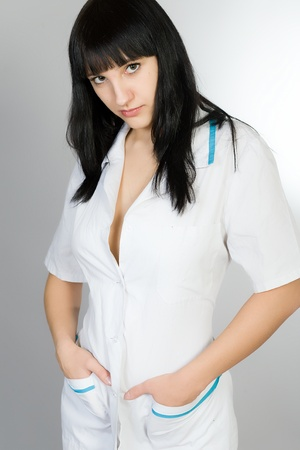 Portrait of the young woman in a white medical dressing gown photo