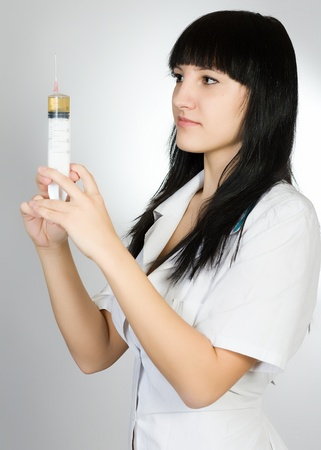 Portrait of the young woman in a white medical dressing gown with a syringe in hands photo