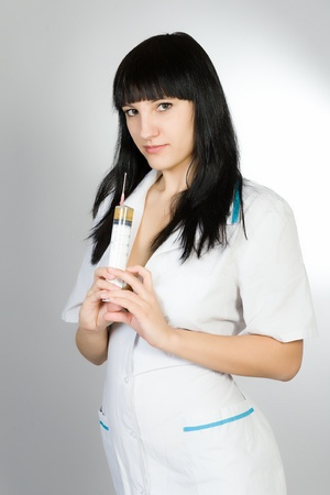 nursing sister: Portrait of the young woman in a white medical dressing gown with a syringe in hands