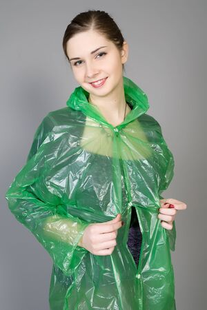 young woman in a green rain raincoat photo