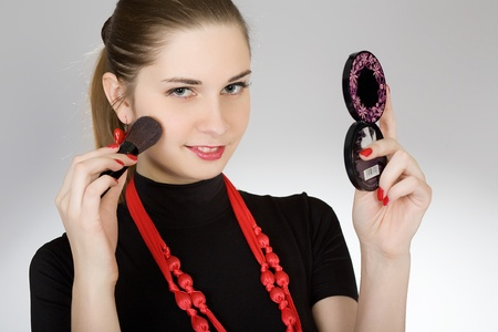 The young beautiful girl does a make-up on the person photo