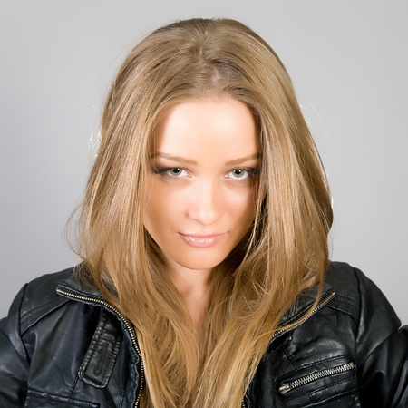 Portrait of the young beautiful girl in a leather jacket photo